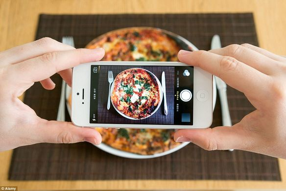 someone taking a photo of pizza on phone