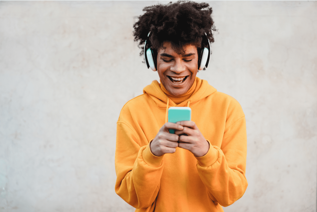 Man smiling, looking at phone